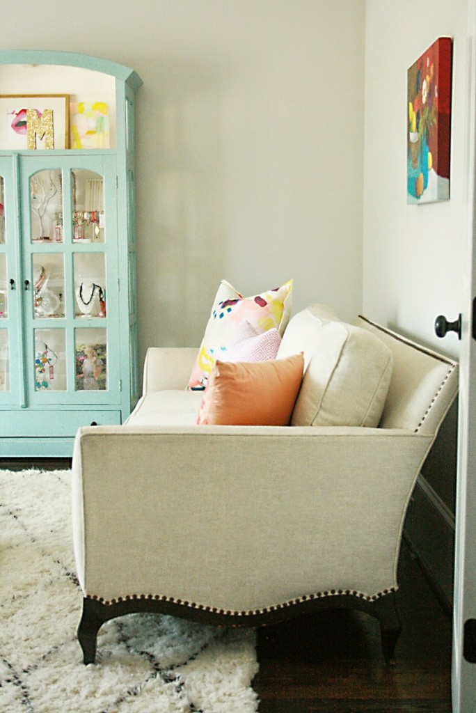 reupholstered white sofa with colorful pillows and jewelry case