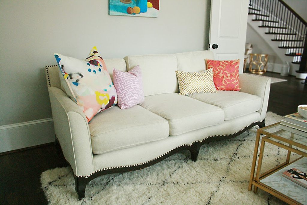 reupholstered white sofa with colorful pillows and shag rug
