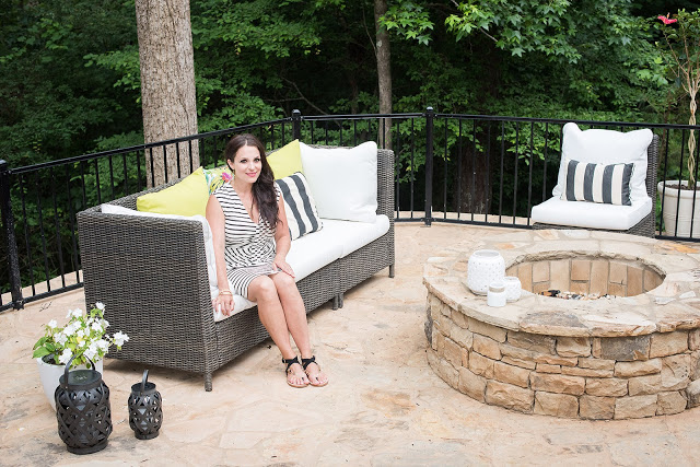 white sectional, black and white outdoor, stone patio, fire pit, backyard landscaping