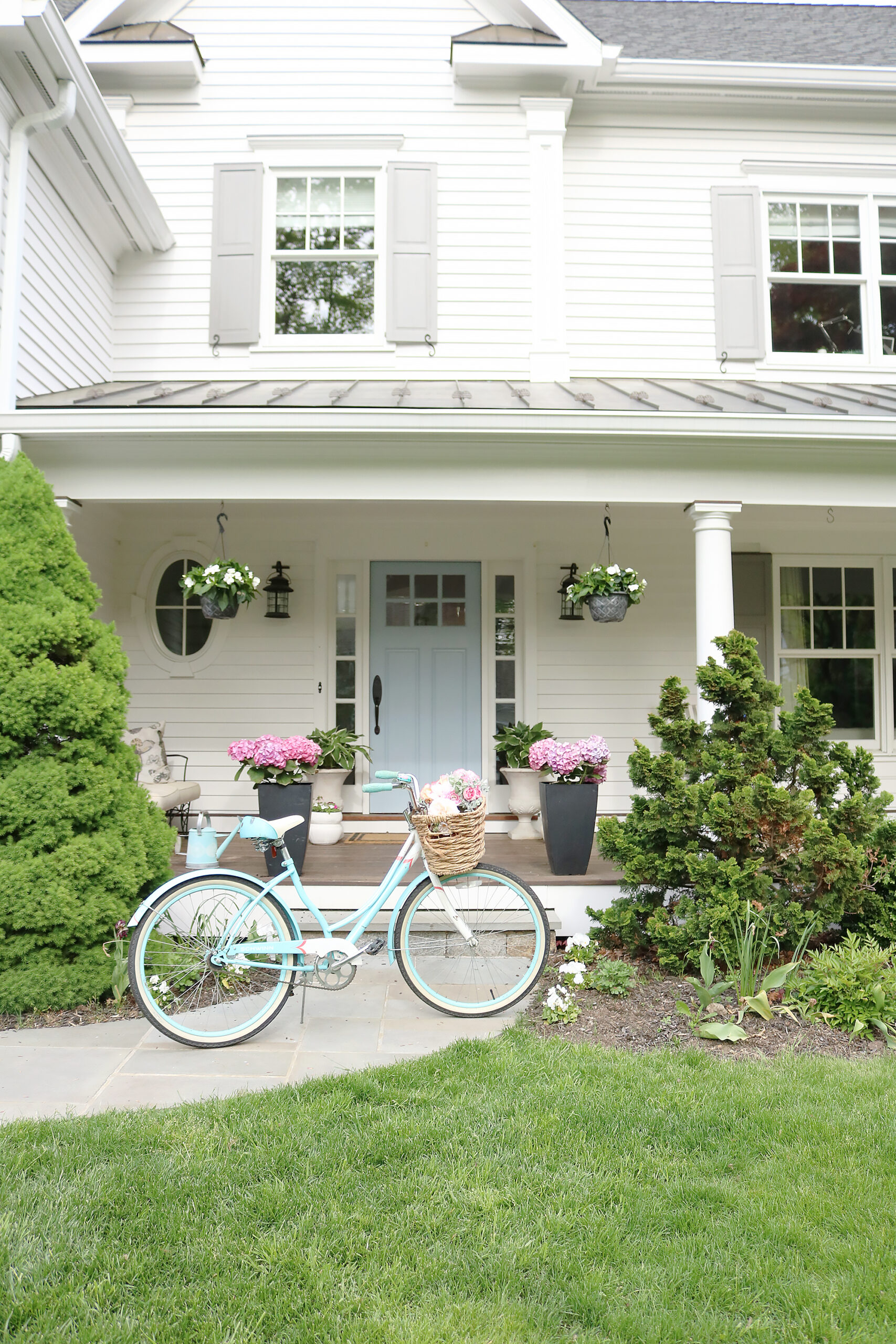 A beautiful home exterior can make or break curb appeal! Sharing 7 easy and simple curb appeal ideas || Darling Darleen Top CT Lifestyle Blogger home exterior | outdoor charm | curb appeal ideas | home exterior ideas | white house with gray shutters | porch swing | shutter | new england charm | blue front door | beach bike | flowering pots front door #darlingdarleen