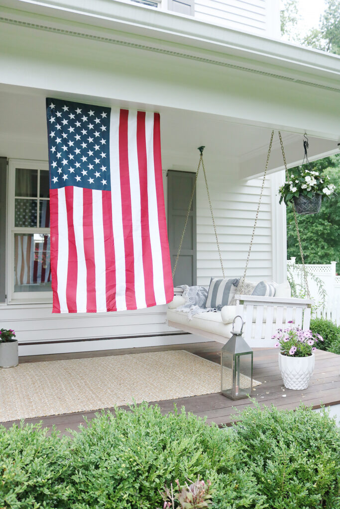 A beautiful home exterior can make or break curb appeal! Sharing 7 easy and simple curb appeal ideas . American flag on front porch. || Darling Darleen Top CT Lifestyle Blogger home exterior | outdoor charm | curb appeal ideas | home exterior ideas | white house with gray shutters | porch swing | shutter | new england charm | blue front door | #darlingdarleen
