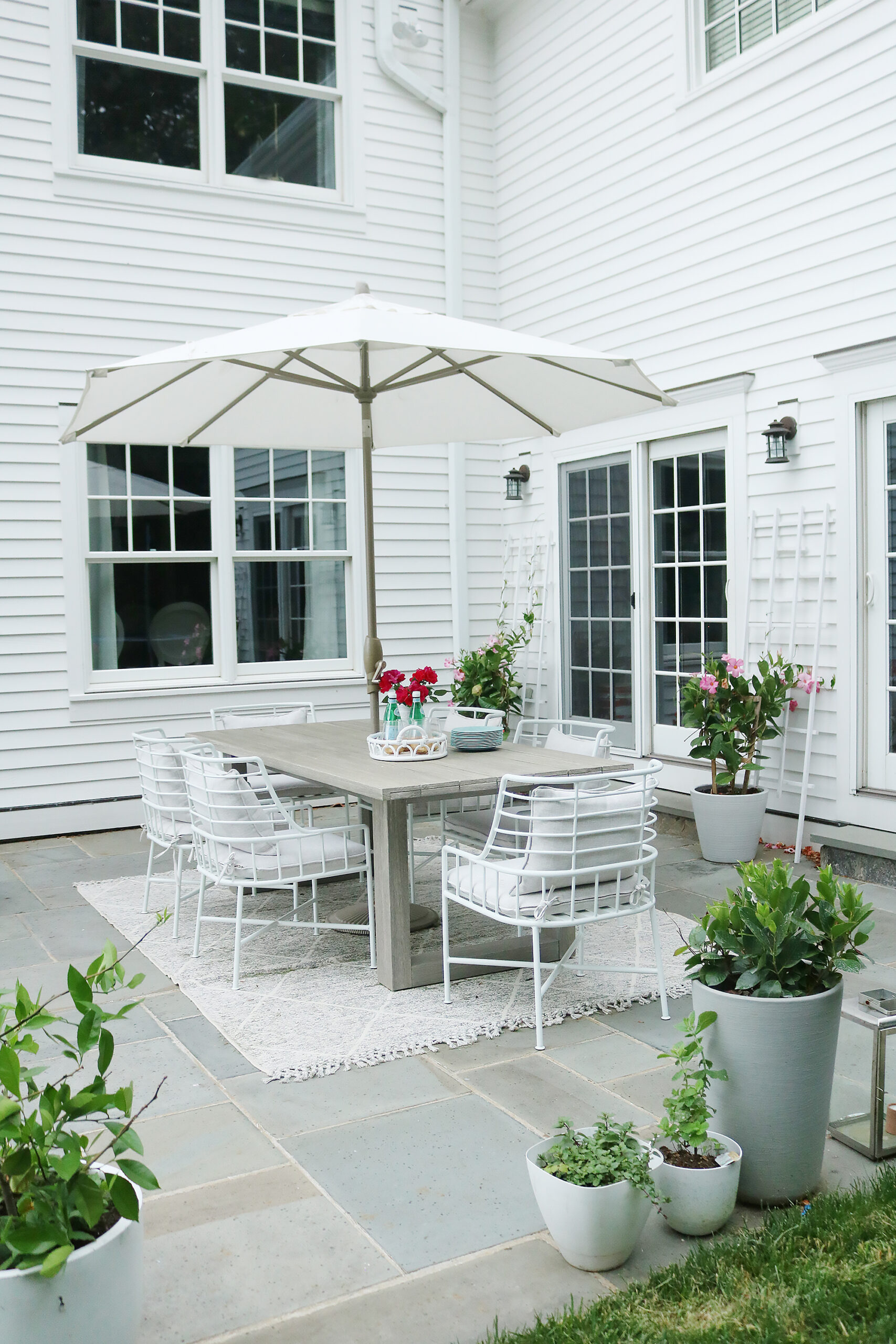 Backyard charm with outdoor dining table modern with white chairs  || Darling Darleen Top CT Lifestyle Blogger home exterior | outdoor charm | curb appeal ideas | home exterior ideas | white house with gray shutters | porch swing | shutter | new england charm | blue front door | #darlingdarleen
